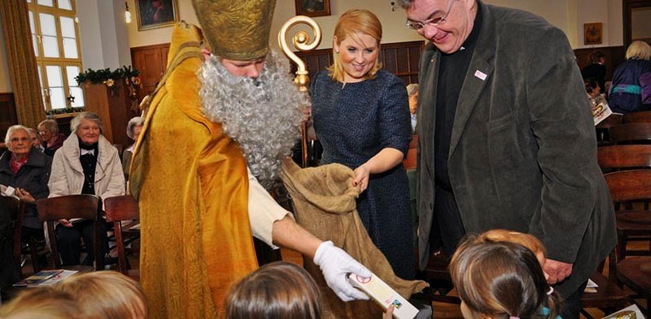 Der Nikolaus, Maite Kelly und Msgr. Austen verteilen Schokonikoläuse an die Kinder des Kinderhauses St. Anton.