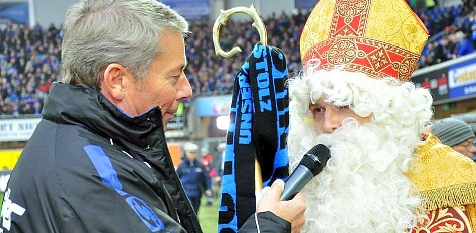 Der Nikolaus steht am Spielfeldrand und spricht in ein schwarzes Mikrofon.