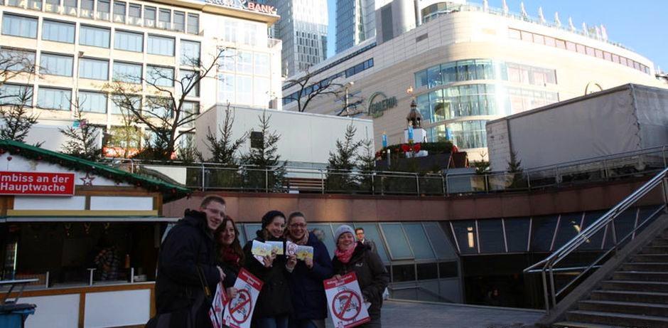 """5 Jugendliche stehen vor einem Weihnachtsmarktstand und halten rot-weiße Plakate und Postkarten der """"Weihnachtsmannfreien Zone"""" in der Hand."""