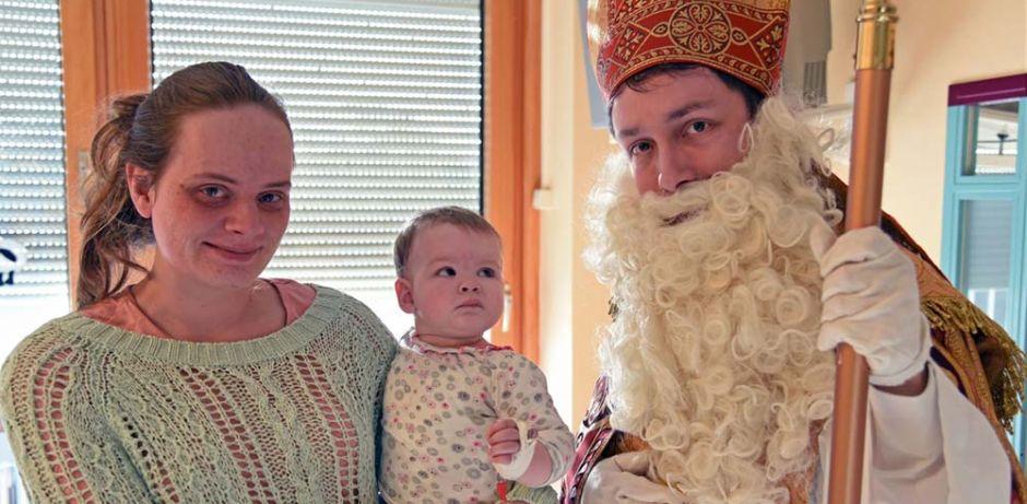 Links ist eine Frau, die ihre kleine Tochter auf dem Arm hat zu sehen. Rechts im Bild steht der Nikolaus und wird von dem kleinen Kind prüfend angeschaut.
