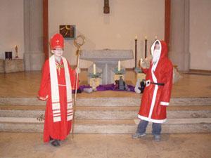 In der Kirche steht links ein kleiner Nikolaus mit roter Mitra und Bischofsstab und rechts der Weihnachtsmann mit einem Jutesack vor dem Altar.