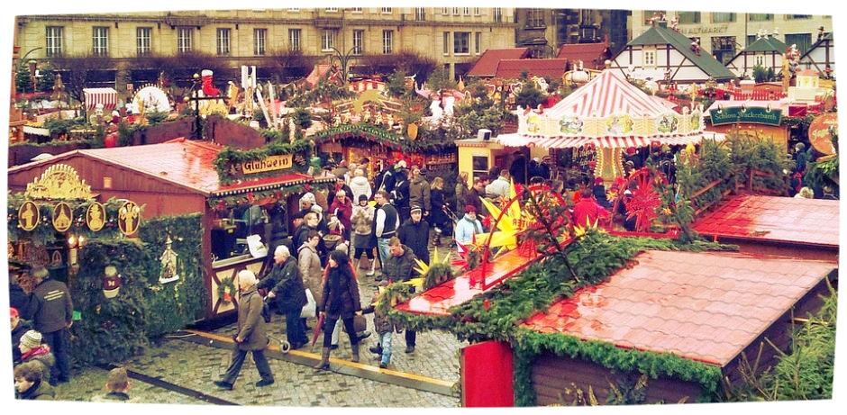 Dicht an dicht stehen Buden auf einem Weihnachtsmarkt - dekoriert mit Tannenzweigen. Mittendrin steht ein Kinderkarussel. (Bild: pixabay)
