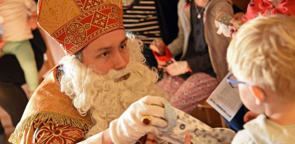 Bischof Nikolaus überreicht kniend einem kleinen Jungen ein Geschenk.