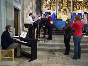 Vorne sitzt ein Mann am Klavier, davor stehen zwei Mädchen, die Querflöte spielen und im Hintergrund stehen eng beieinander 6 Sänger/-innen.
