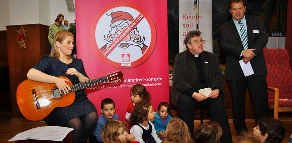Maite Kelly, Msgr. Austen und Christian Poka (Leitung Altenheim Kreszentia Stift) begrüßen die Kindergartenkinder aus dem Kinderhaus St. Anton und die Altenheimbewohner.