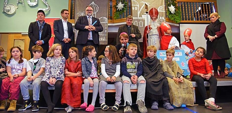 Die im Untertitel erwähnten Leute stehen bzw. sitzen auf einer Bühne und lauschen den Worten von Bischof Stefan Oster, der hinter den sitzenden Kindern kniet.