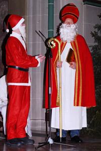 Links steht der Weihnachtsmann mit roter Zipfelmütze und rechts neben ihm der Nikolaus mit roter Mitra und goldenem Bischofsstab.