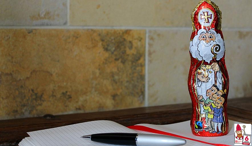 Der Schokonikolaus steht auf einem aufgeschlagenen Heftchen, auf dem noch ein silber-schwarzer Kugelschreiber liegt und ein rotes Band als Lesezeichen dient.
