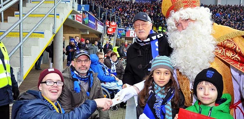 Der Nikolaus überreicht einem Jugendlichen einen Schokonikolaus. Vor dem Nikolaus stehen zwei Kinder und im Hintergrund ist Heinz Paus, Präsident des Bonifatiuswerkes, zu sehen.
