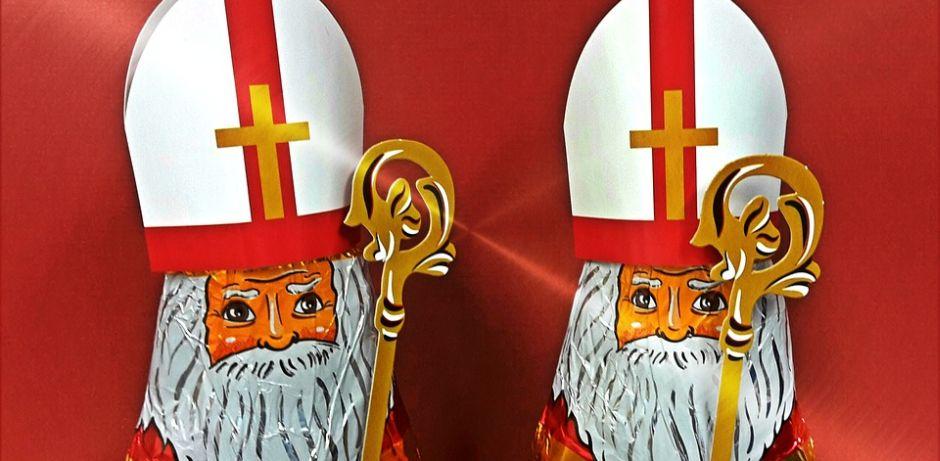 Zwei Schokoladennikoläuse mit Mitra und Bischofsstab vor rotem Hintergrund