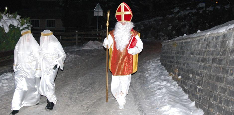 Gemeinsam mit zwei in weiß gekleideten Engeln läuft der Nikolaus mit roter Mitra und goldenem Bischofsstab die schneebedeckte Straße entlang.