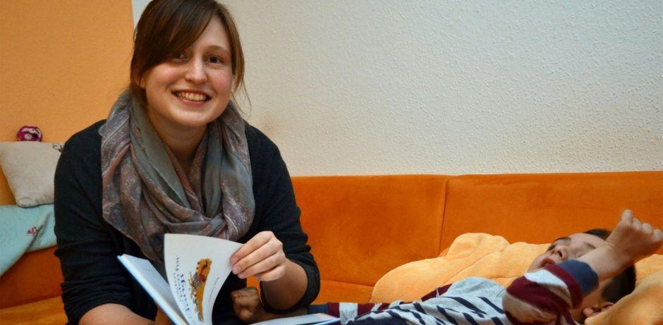 Eine ehrenamtliche Helferin blättert in einem Kinderbuch. Neben ihr liegt auf dem orangenen Sofa einkrankes Kind, das von der jungen Frau betreut wird. Morten lebt mit einer unheilbaren Krankheit, die sein Nervensystem Stück für Stück zerstört.