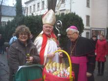 Ein verkleideter Nikolaus steht neben dem Weihbischof Pieschel und hält einen Korb voll mit Schokonikoläusen in der Hand.