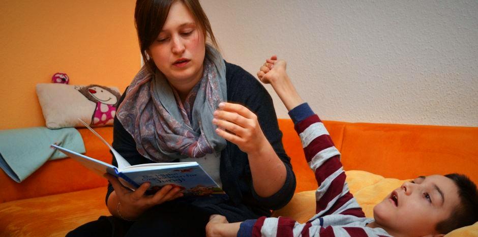 Eine ehrenamtliche Helferin liest einem kranken Jungen, der auf einem Sofa liegt, etwas aus einem Buch vor.  Morten mag es, wenn ihm die ehrenamtliche Hospizhelferin, Bianca Stanulla, vorliest.
