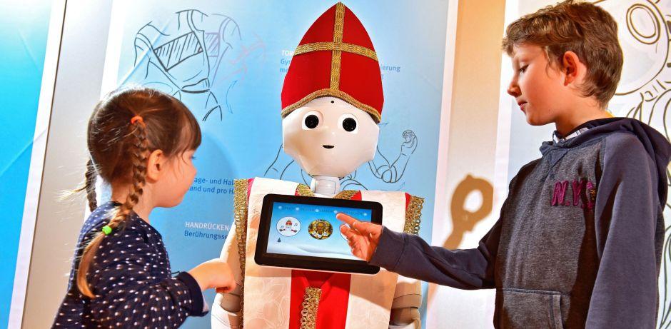 In der Mitte des Bildes sieht man einen weißen Roboter mit schwarzen Augen, der eine Mitra und ein Bischofsgewand trägt. Links und rechts daneben stehen ein Junge und ein Mädchen,  die auf einen Touchscreen vor der Brust des Roboters tippen.