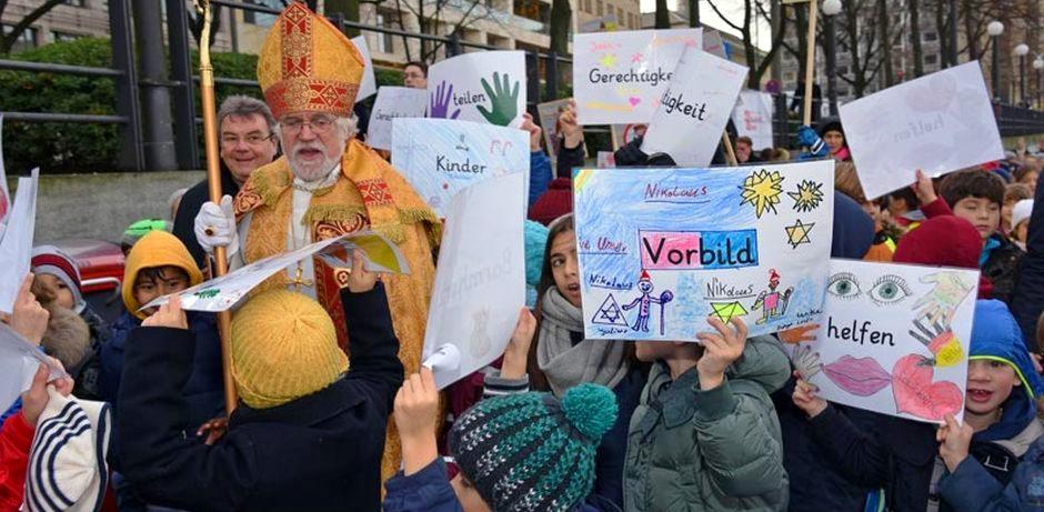 Nikolaus wird von Kindern umringt, die bunte Plakate in die Luft halten und auf denen Worte wie: Vorbild, helfen, Kinder, Gerechtigkeit und teilen stehen.