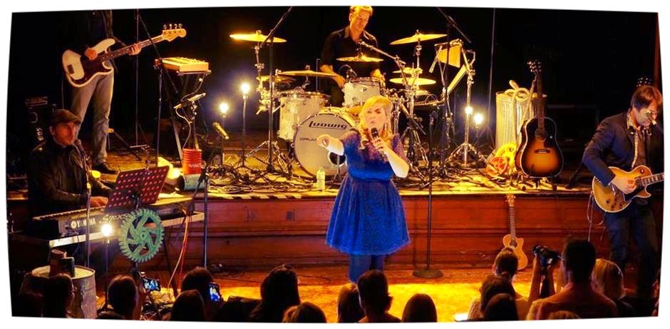 Maite Kelly steht mit einem blauen Kleid auf einer Bühne und singt in das Mikrofon, das sie in der linken Hand festhält. Mit der rechten Hand zeigt sie auf das Publikum. Neben und hinter ihr stehen die Bandmitglieder.