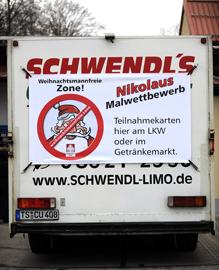 """Auf dem hinteren Teil eines LKWs hängt ein Banner, auf dem das Logo der """"Weihnachtsmannfreien Zone"""" zu sehen ist und der Malwettbewerb beworben wird"""