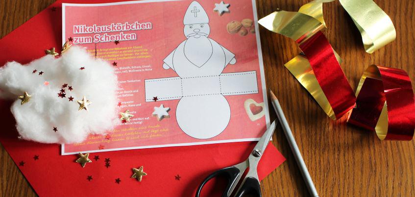 Auf einem Holztisch liegt der Bastelbogen für den Nikolaus in Kombination mit einem Körbchen. Links daneben liegt Watte mit goldenen und roten Sternen darauf. Rechts ist Goldpapier, Stift, Schere zu sehen. Unter der Schablone liegt roter Pappkarton