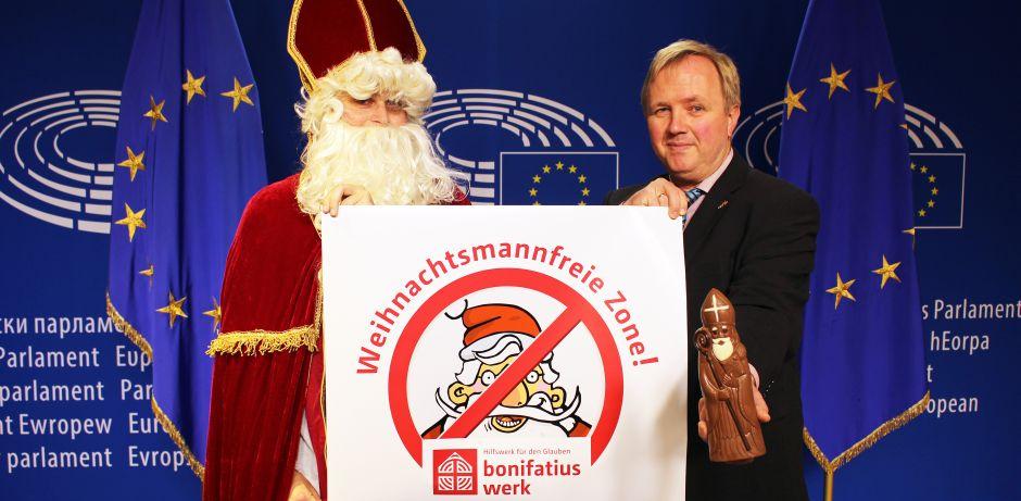 Links steht der heilige Nikolaus und rechts im Bild der Europaabgeordneter Arne Gericke. Zusammen halten sie das Logo der Weihnachtsmannfreien Zone in der Hand. Der Abgeordnete zeigt zusätzlich noch einen Schokonikolaus in die Kamera.