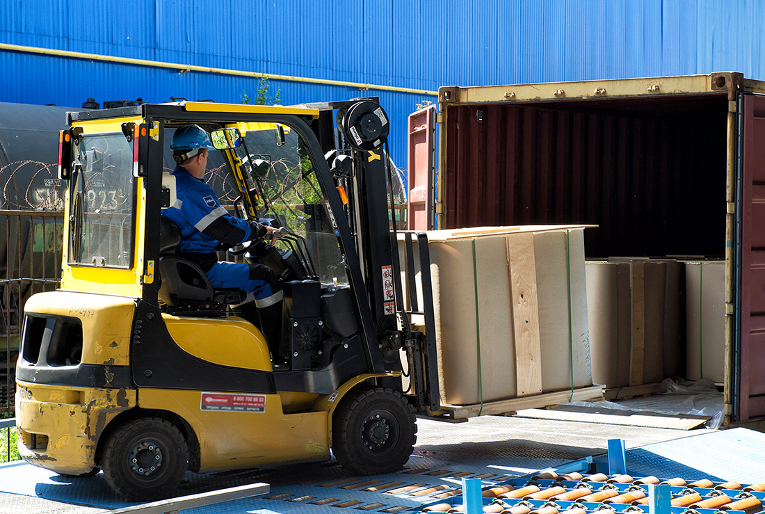 Forklift  loading the IBC in to the  40 ft. container mounted  on the railcar