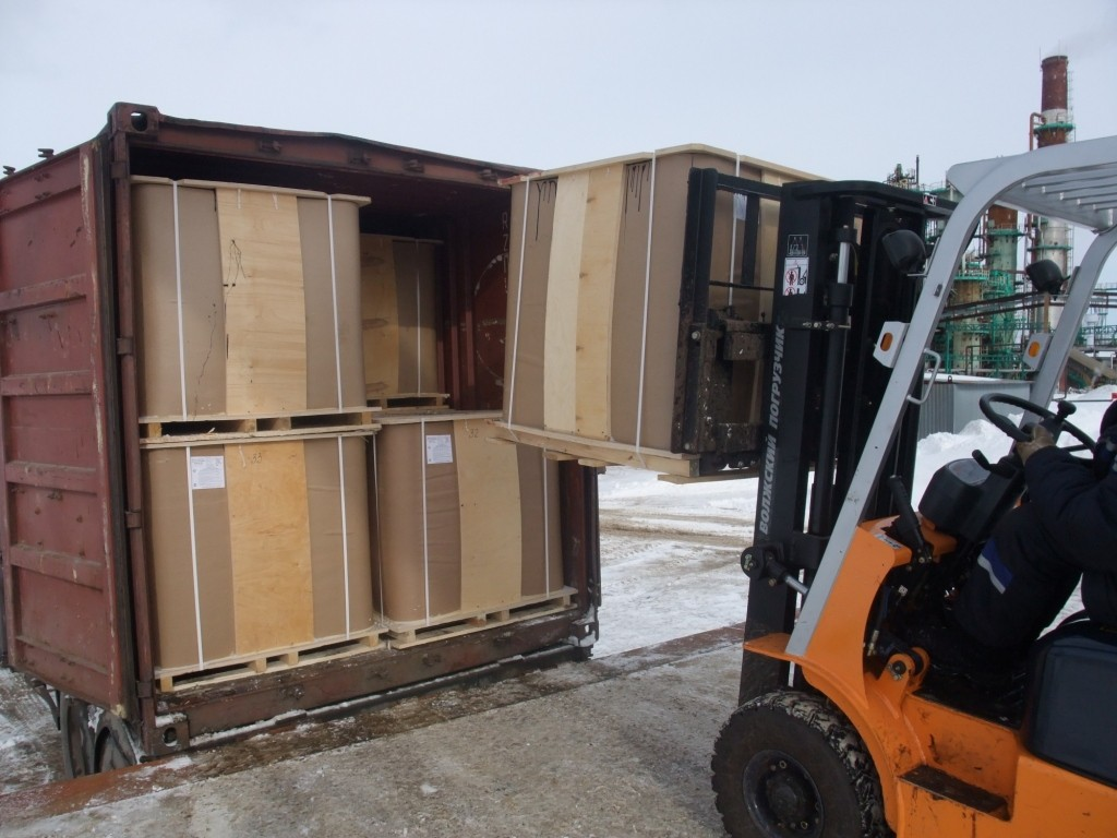 Forklift  loading the IBC in to the  20 ft. container mounted  on the truck