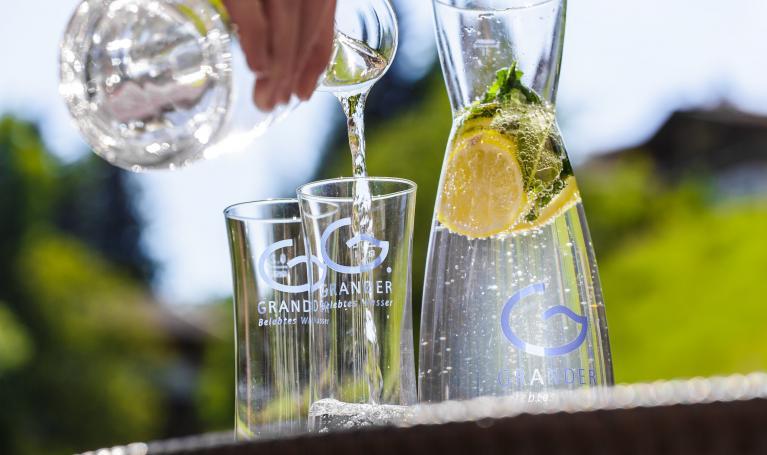 Glaskaraffe und Gläser mit Granderwasser