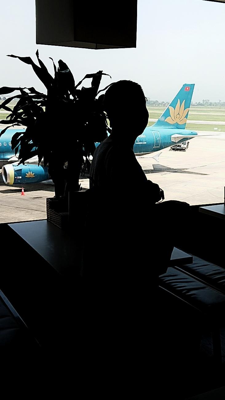 Erkundungstour - zentrales Hochland  - Vietnam – Erkundungstour – Ly und Heiko – Viethouse – Flugzeug Vietnam Airlines im Sonnenlicht – Vorfeld – Konturen einer Frau – Gegenlicht