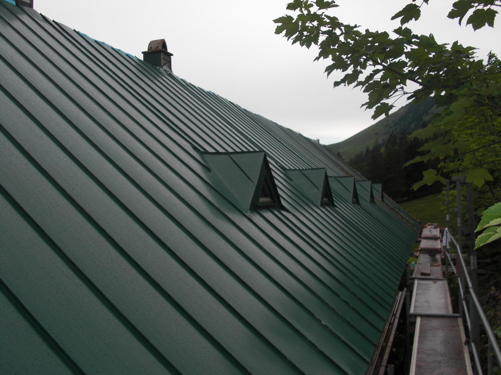 Herrenalm: Generalsanierung des Dachs der Herrenalm. Blecheindachung mit Erkerfenstern.