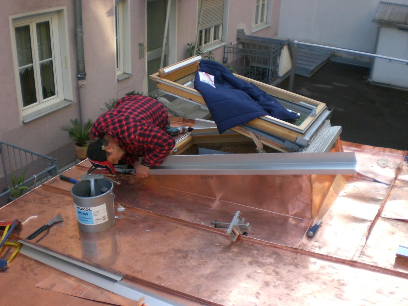 Garagenhof München: Blechdacheindeckung eines Garagenhofs, alle Garagen mit Fenstern und zahlreichen Ausfalzungen.