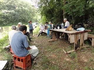 食後、木陰でミーティング 学生4名の研修活動内容等