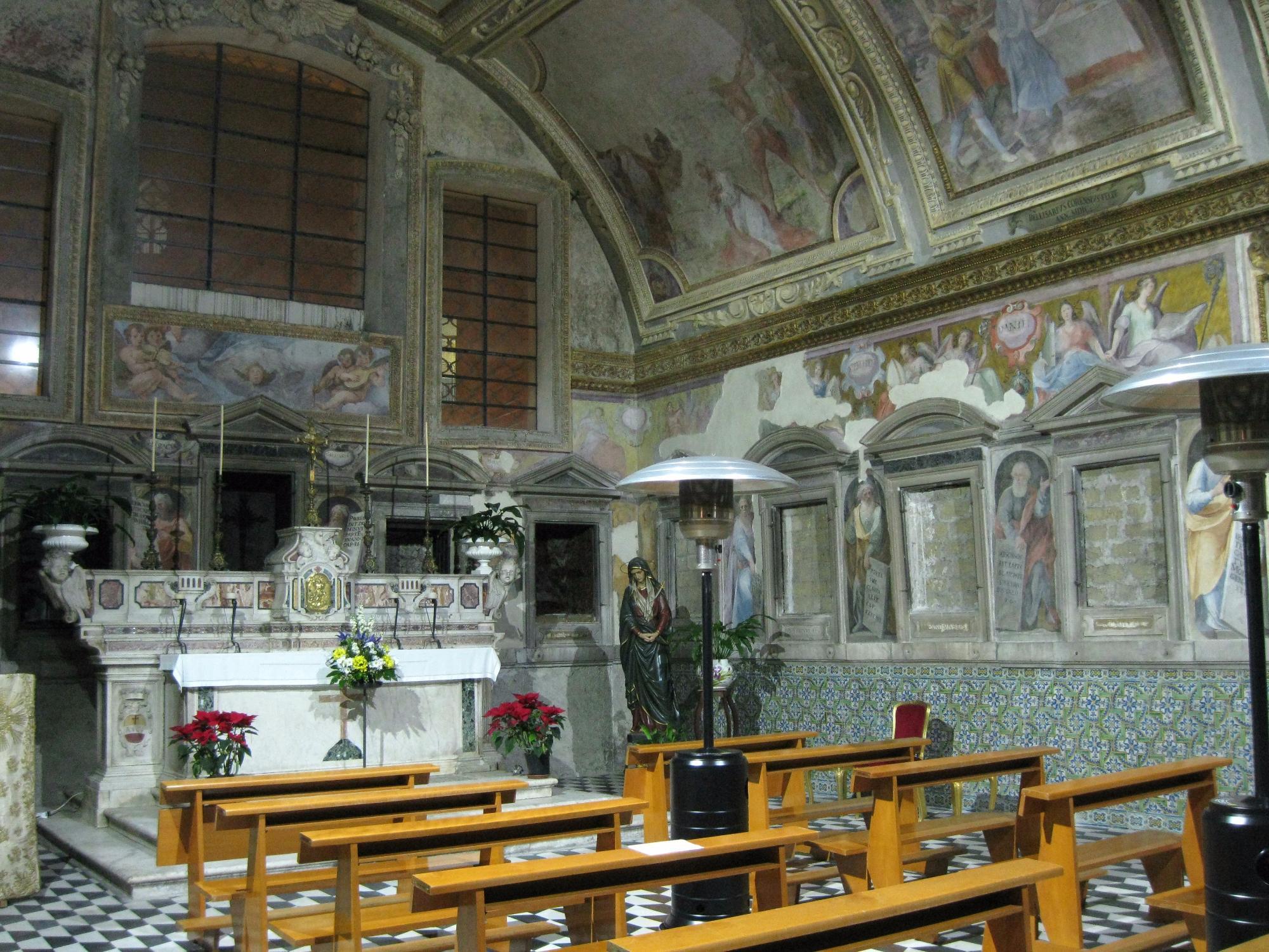 """La parete prospiciente, con le nicchie ancora murate e l'Altare maggiore, che attualmente custodisce le reliquie dei Martiri; l'affresco in alto, dipinto dal CORENZIO e aiuti, rappresenta il """"Martirio di S. Orsola"""""""