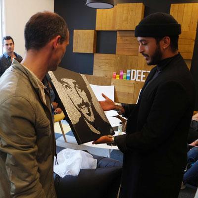 Le peintre performer Erik black remet son tableau au chanteur Slimane lors d'un show case.