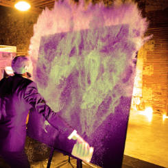 live painter throws glitter on stage