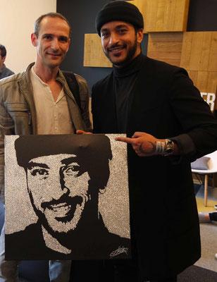 Erik black et Slimane posent avec le portrait du chanteur