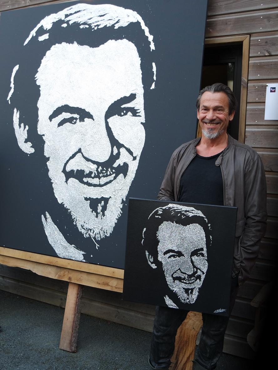 Le chanteur Florent Pagny prend la pose à côté de son portrait glitter painting réalisé par le peintre performer Erik Black