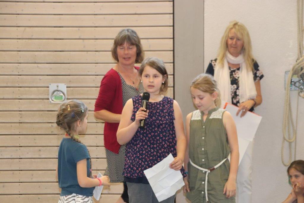LEa, Mila und Ella übergeben den Scheck an die Vertreterin der CLOWNS vom Dienst