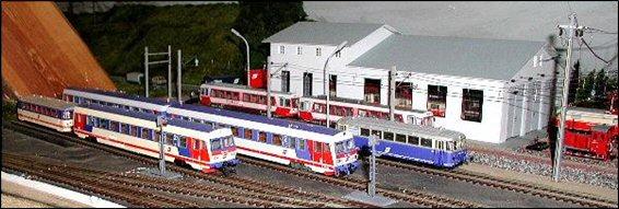 Abb. 24, Abstellgruppe im neu gestalteten Alpenbahnhof H0 mit Fahrzeugen für den Regionalverkehr, dahinter die selbst gebaute Lokomotivhalle in H0e, deren Einfahrtstore mittels Motor geöffnet oder geschlossen werden können