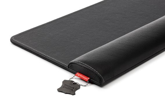 Eine schwarze breite Handgelenkauflage für Büroarbeiten vor weißem Hintergrund
