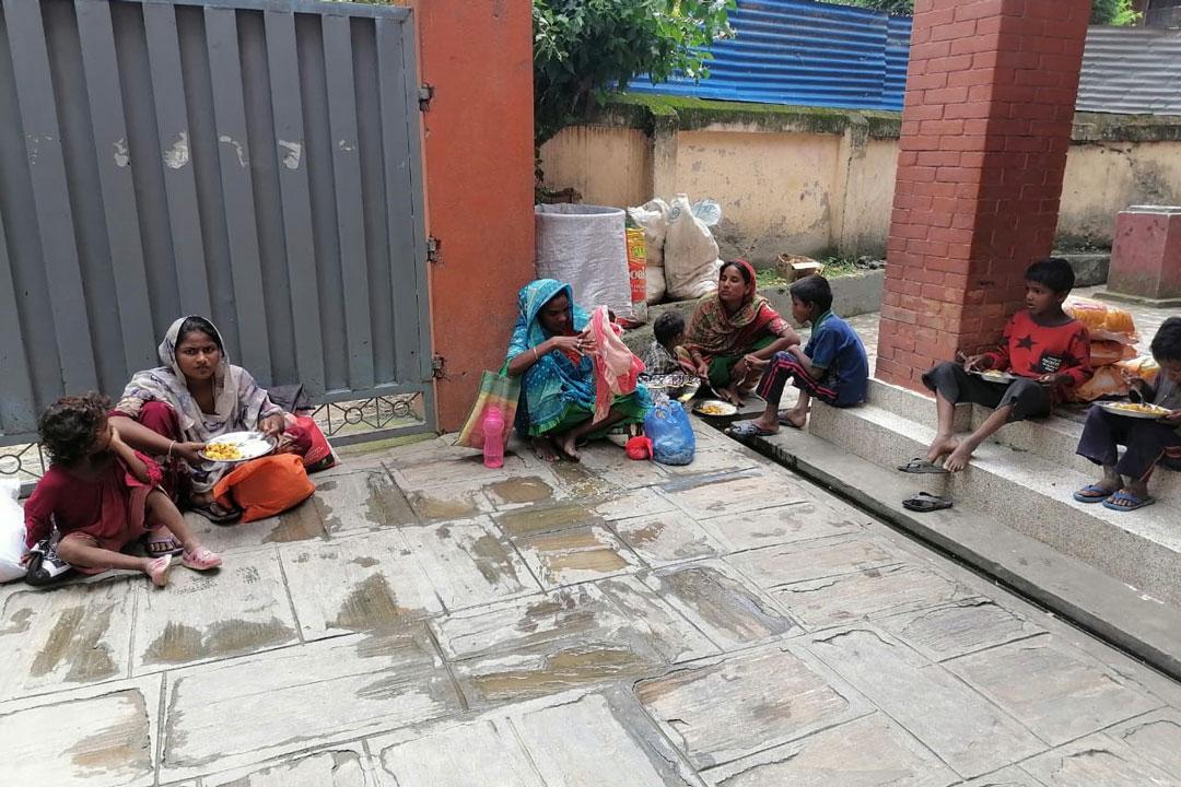 Familie mit Kindern, die von uns neben den Lebensmittelpaketen auch eine Portion Dal Bhat bekommen haben.