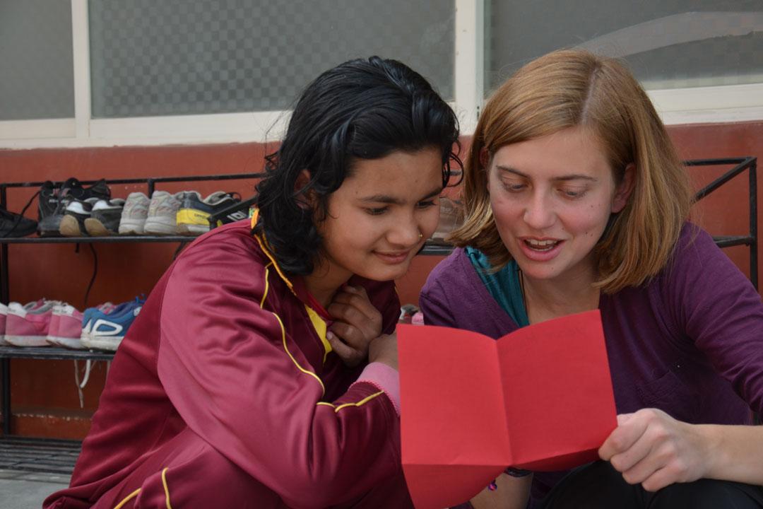 Praktikantin Janina liest Manisha ihren Brief vor.