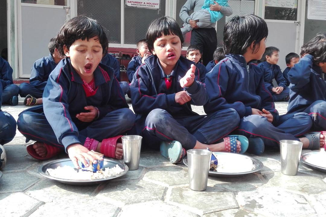 Ganga und Dikshya lassen sich das Popcorn zum Tiffin schmecken.