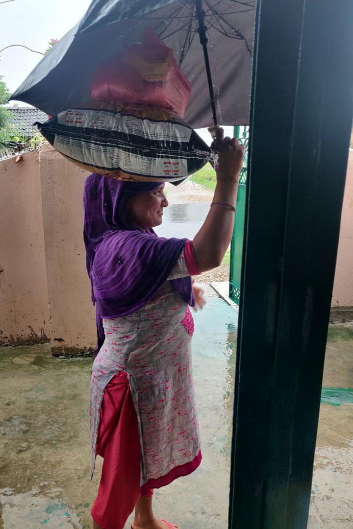 Frau in Nepalganj trägt das von uns erhaltene Lebensmittelpaket nach Hause