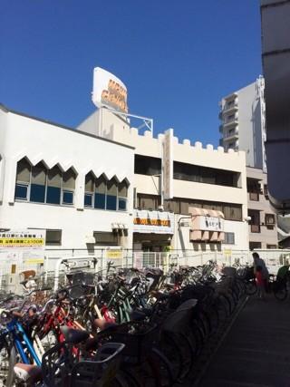 自転車置き場があるので通り抜けます 前に見える白いビルの二階です