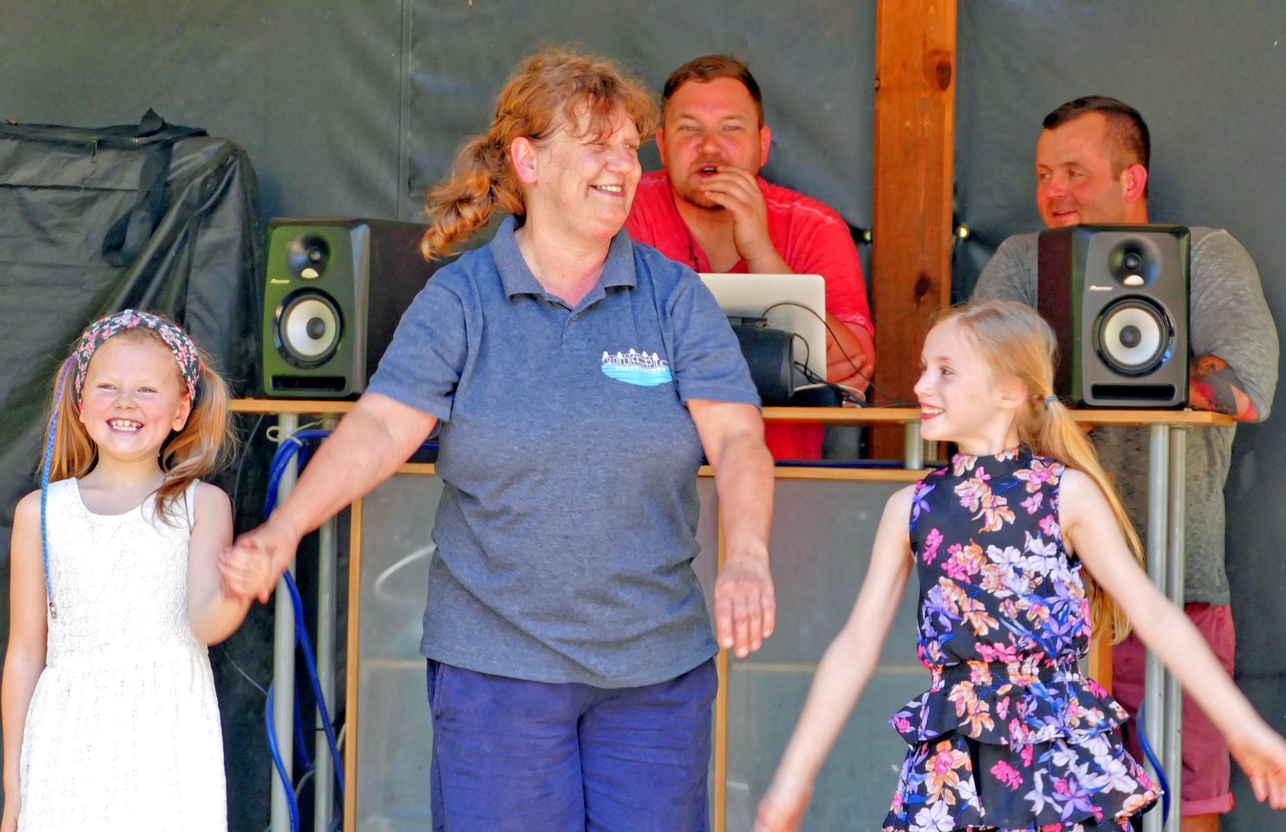 Die Plattenwirtin begrüßt zusammen mit den beiden Vortänzerinnen die Gäste.