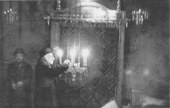 En el interior de la Sinagoga barcelonesa resplandecen las luces de los candelabros. pero esta interesantísima fotografía ha sido, como puede suponerse, difícil de obtener. Representa al rabino en el momento culminante en que dirige la oración de los hebr
