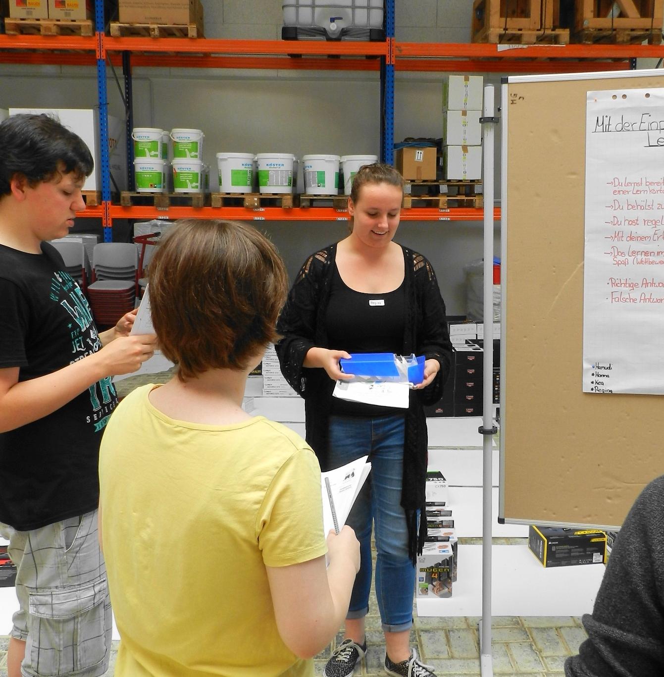 Regina zeigt ihren Mitschülern Timo und Katrin den Umgang mit einer Lernkartei.