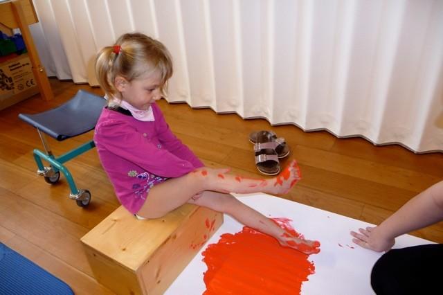 Mit den Füßen malen.