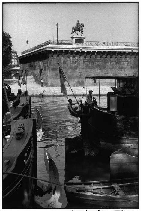 FRANCE. Paris. 1957. The Pont Neuf bridge with the statue of King Henry IV and barges along the Seine.