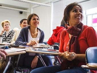 Frauen sitzen in einem Seminar und hören jemandem zu, der über die ERGO Seminar-Versicherung spricht